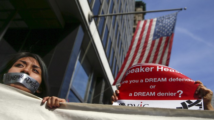 """A young woman with tape on her mouth that reads """"Hungry4aDream"""" stands in front of an American flag."""