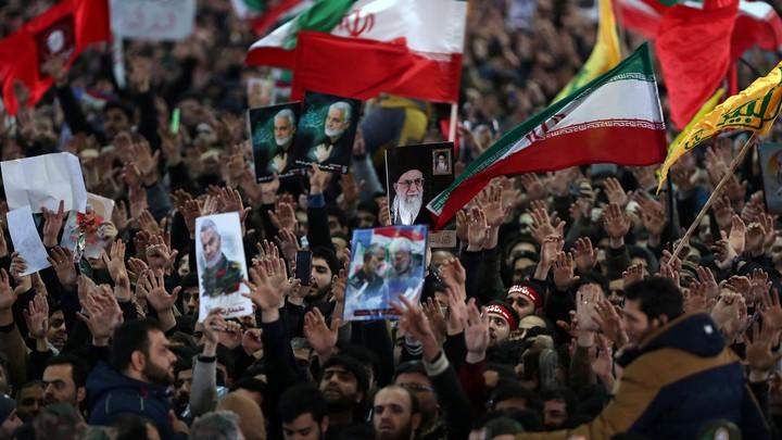 Iranians carry pictures of Iranian Supreme Leader Ayatollah Ali Khamenei and Qassem Soleimani during Soleimani's funeral.