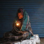 A man lights a cigarette in Old Delhi, India.