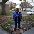 A young black boy stands on a sidewalk