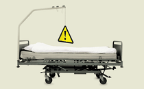A yellow warning sign hangs above a gurney.