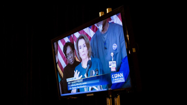 A screen shows Representative Nancy Pelosi, then House minority leader, giving a press conference via C-SPAN.