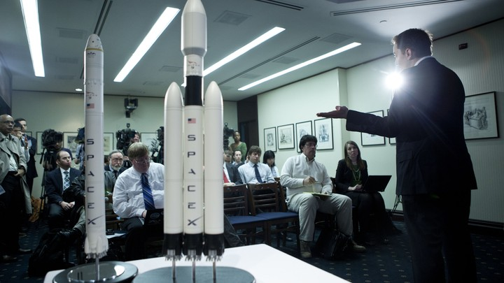 "A person gestures to two models of rockets labeled ""SpaceX."""
