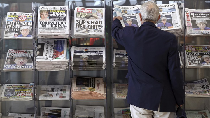 A man picks up a newspaper reporting on the outcome of the U.K.'s general election in London on June 10, 2017.