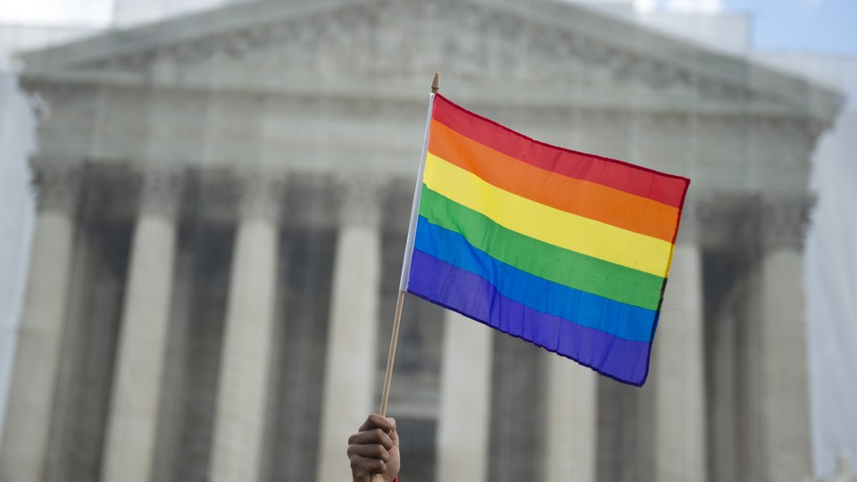 A hand holding a rainbow flag outside of the Supreme Court