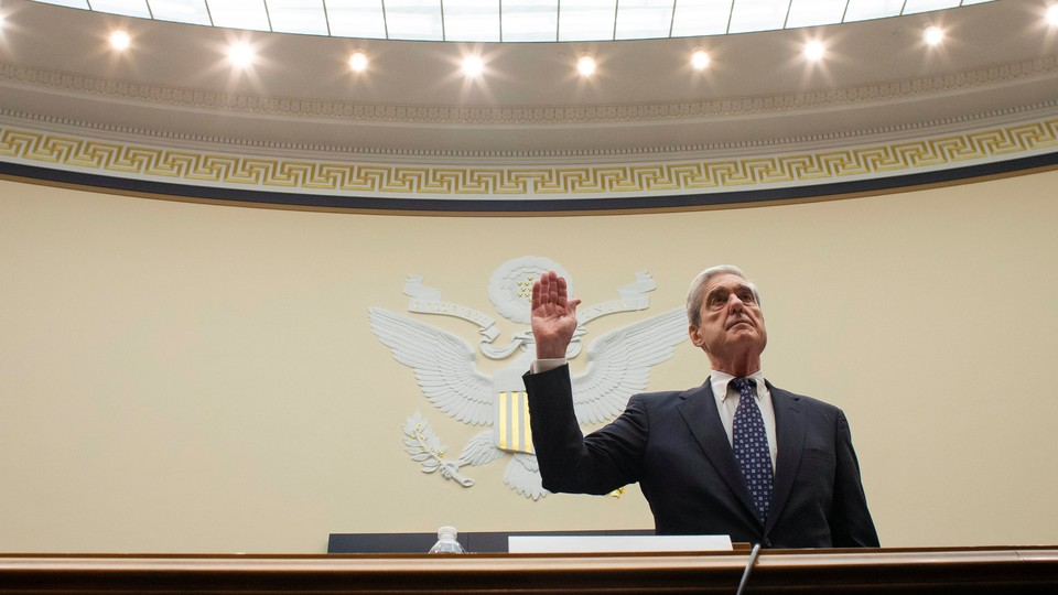 Robert Mueller lifts his right hand up while swearing in to testify in front of the House Judiciary Committee.
