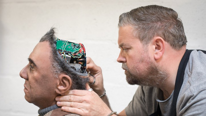 A human fixes a human-looking robot