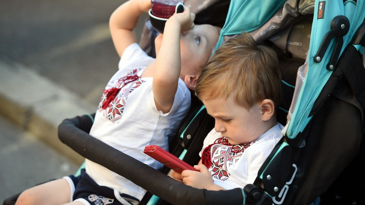 A young child plays with a phone while his brother drinks juice.