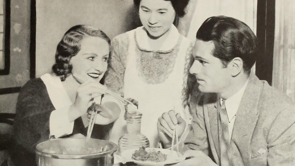 A man and woman eat dinner with their maid.