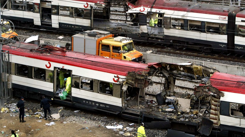 Railway workers remove debris from the wreckage of a bombed public train in Madrid on March 12, 2004.