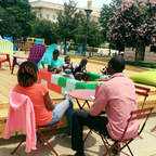 Children and adults sit on and around a deck with multi-colored chairs and giant LEGOs.
