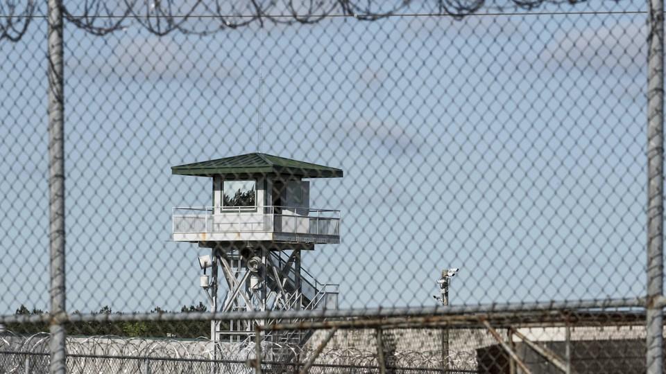 A jail watchtower seen through a fence