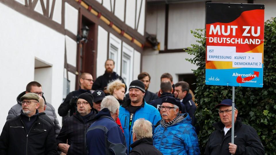 Alternative für Deutschland hold signs outside a Holocaust memorial.