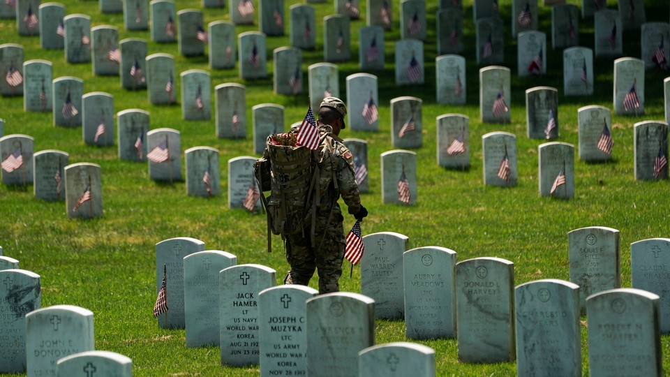 An Old Guard places American flags by headstones in Arlington National Cemetery.