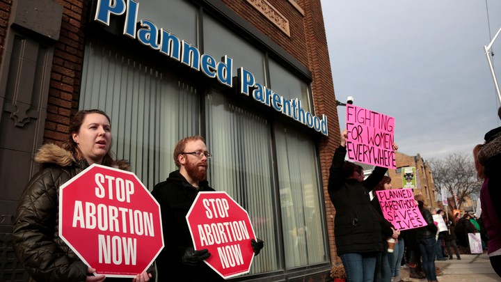 Protsters stand outside a Planned Parenthood clinic holding signs.