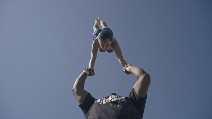 A cheerleader does a handstand while balancing on a teammate's palms.