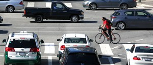 A cyclist maneuvers his way through downtown Los Angeles traffic on Tuesday, Sept. 16, 2014.