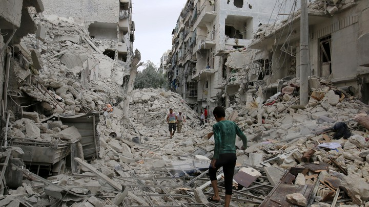 People inspect the damage left after an airstrike hit the rebel-held neighborhood of Tariq al-Bab Friday in Aleppo, Syria.
