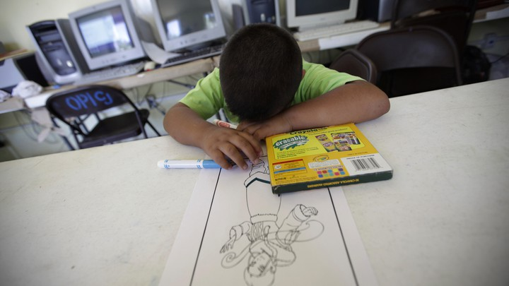 A child rests his head on the table next to a box of markers and a coloring page.