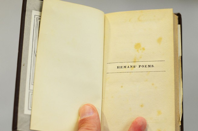 Someone opens a book to its title page.
