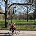 photo: A cyclist rides past a closed Victoria Park in East London.