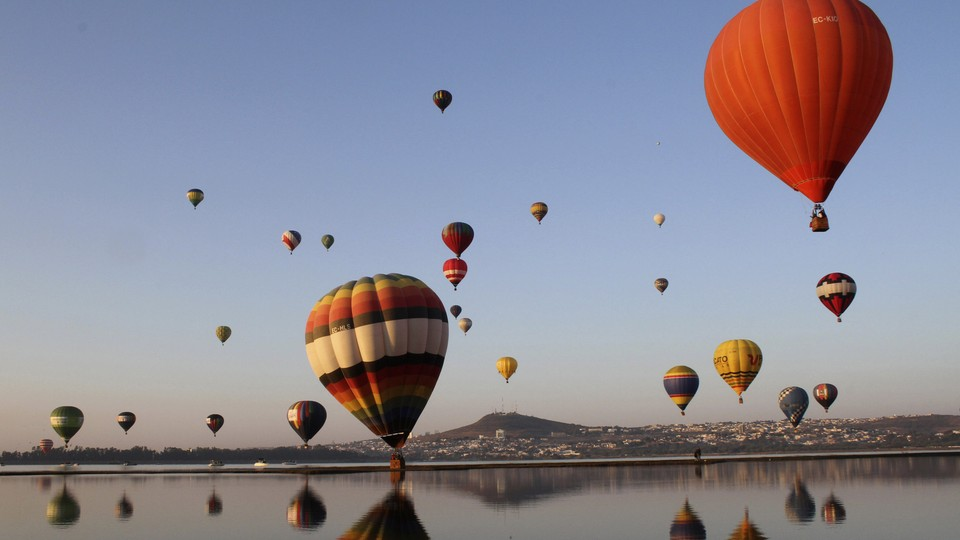 Hot-air balloons and their reflections along a coastline