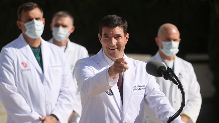 Trump's physician, Sean Conley, standing at a podium. He is smiling and pointing his finger.