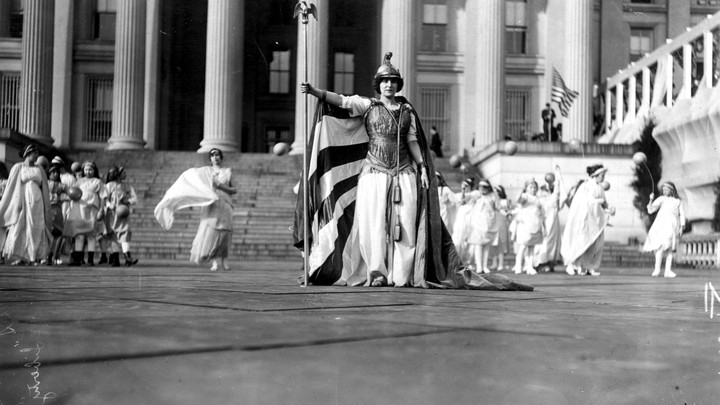 Suffrage pageant participants dressed in white stand in front of the Treasury Building, in Washington, D.C., on March 3, 1913.