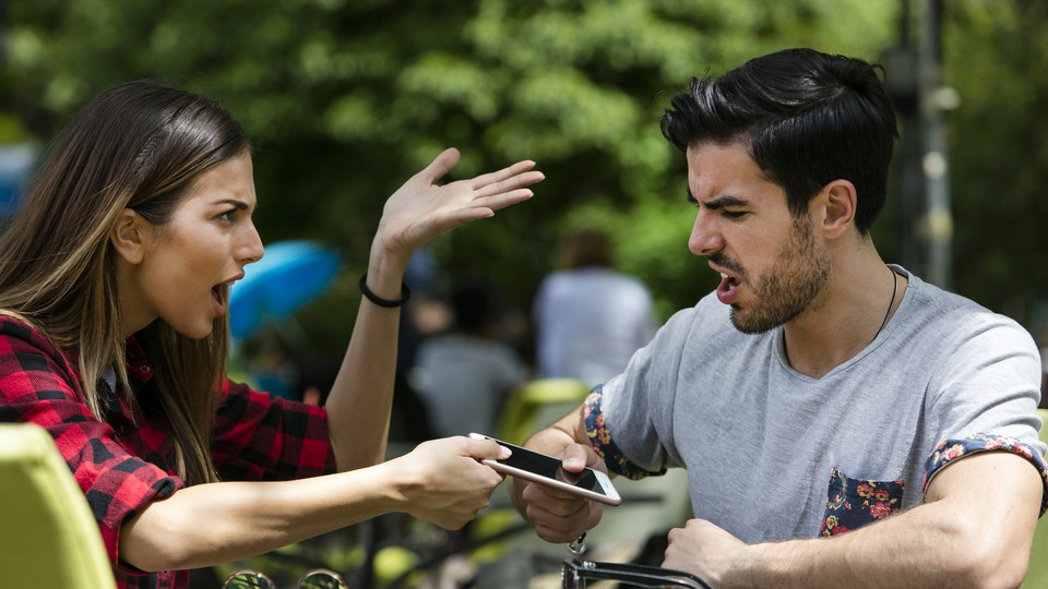 A couple argues while fighting over a smartphone.