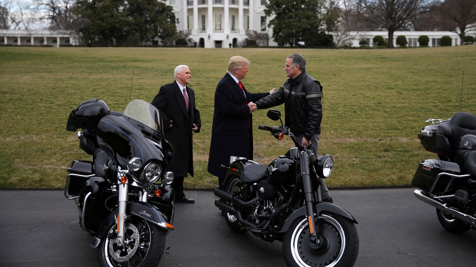President Trump shakes hands with the Harley-Davidson CEO in front of motorcycles.