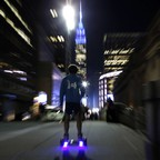 A young man rides a hoverboard along a Manhattan street toward the Empire State Building in New York