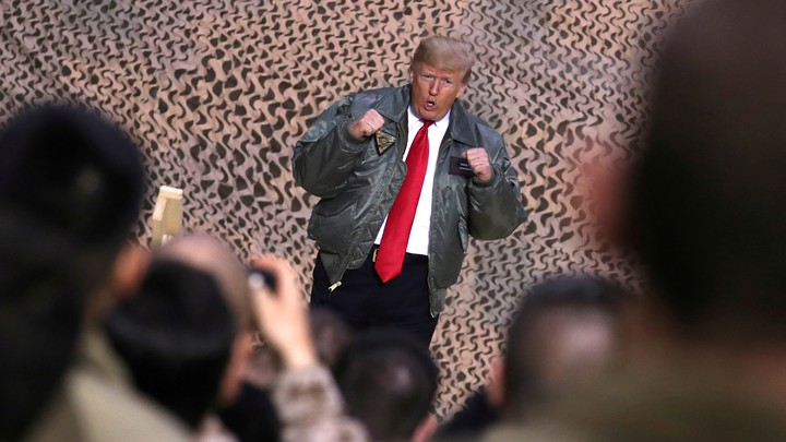 Donald Trump poses in front of cameras and U.S. troops.
