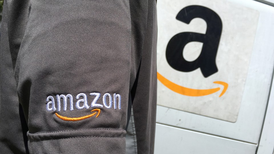 An Amazon driver stands next to an Amazon truck.