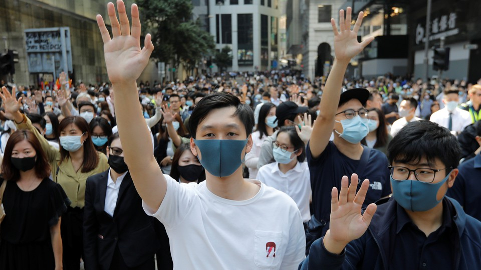 A crowd of Hong Kong protesters in masks raise their hands in unison.