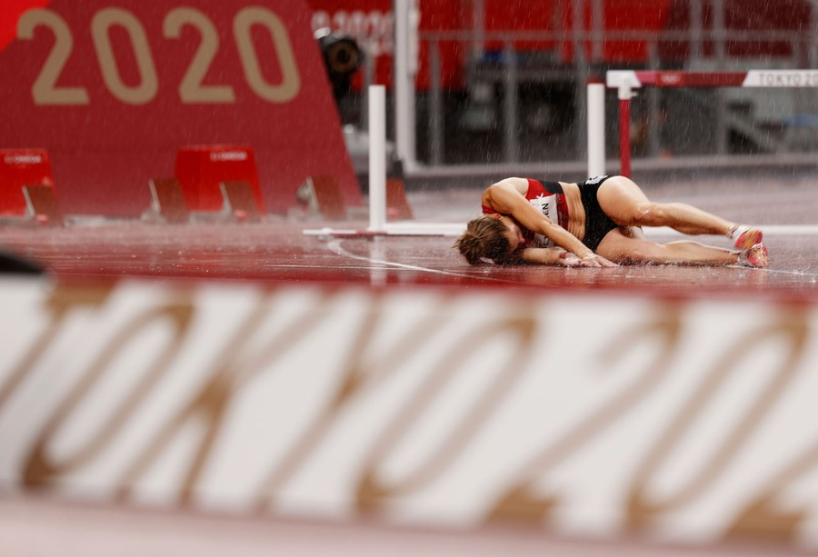A runner lies prone on the track after an event.