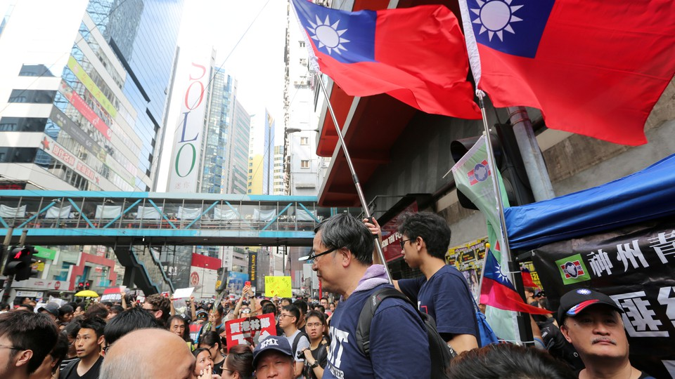 Protesters wave Taiwanese flags at a rally in Hong Kong.