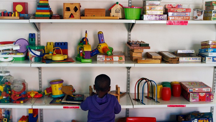 A kid stands in front of shelves of toys