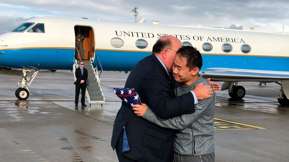 A man wearing a suit hugs the Chinese American graduate student Xiyue Wang in Zurich, Switzerland, on a tarmac in front of an American diplomatic jet.