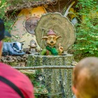 A goblin figure in a tree trunk talks to visitors at a forest theme park.