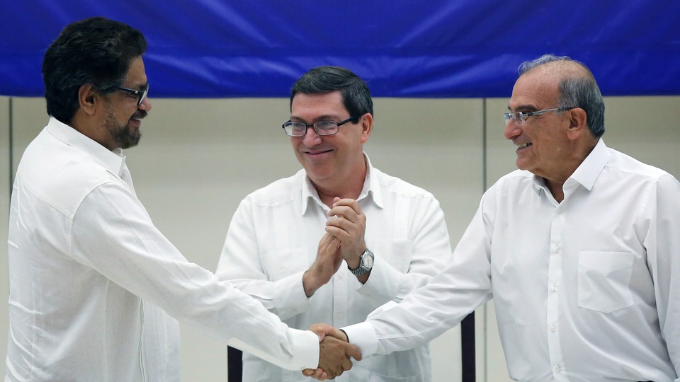 FARC lead negotiator Ivan Marquez, left, and Colombia's lead government negotiator Humberto de la Calle, right, shake hands while Cuba's Foreign Minister Bruno Rodriguez looks on, after signing a final peace deal in Havana, Cuba.