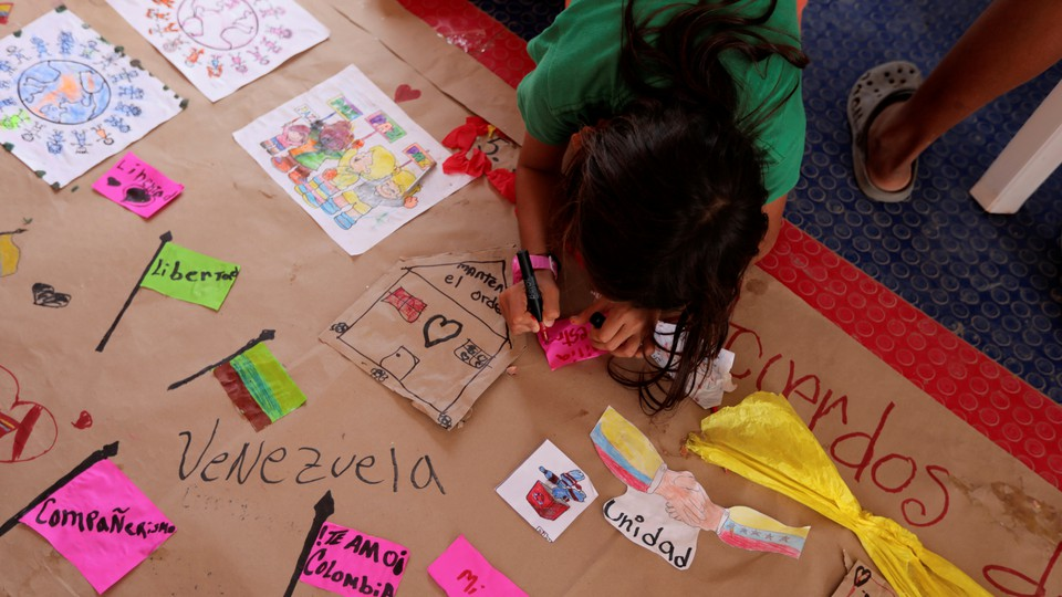 """A girl in a green shirt draws hearts and houses on a paper labeled """"Venezuela."""""""