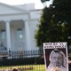 """A protestor holds a sign that says """"Where is Khashoggi?"""" outside the White House."""