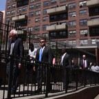 Sanders walking in front of a large apartment building with men in suits