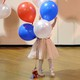 A little girl plays with balloons