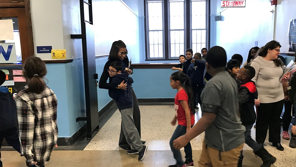 A child in a crowded hallway hugs the principal.