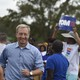"""Tom Steyer arrives at the Charleston Blue Jamboree. He's flanked by supporters holding """"Tom 2020"""" signs."""