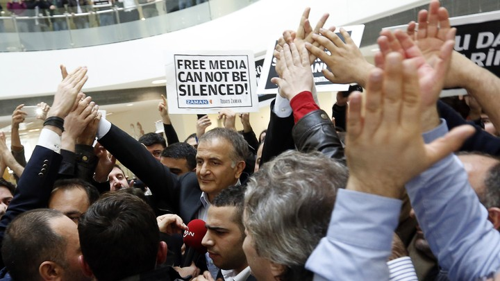 """The Zaman editor in chief, Ekrem Dumanli, stands in a crowd of supporters and newspaper employees holding signs that say, in English and Turkish, """"Free media cannot be silenced."""""""