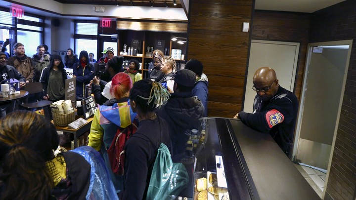 Demonstrators gather in a Starbucks as a police officer watches them.