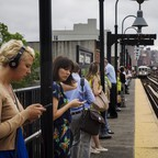 Commuters line a subway platform as a train approaches.