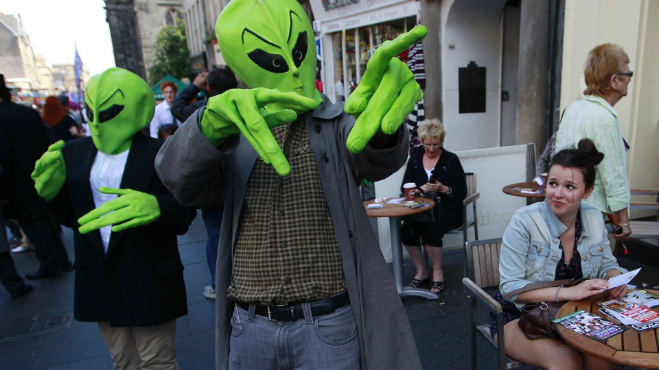 Two people dressed in green alien heads and hands gesture on a busy street.